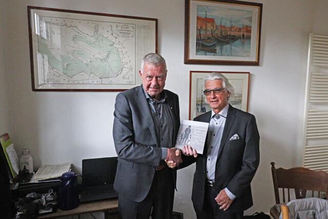 Voorzitter Kees Coppens (l) ontvangt het eerste exemplaar van Jacques van Eekelen.